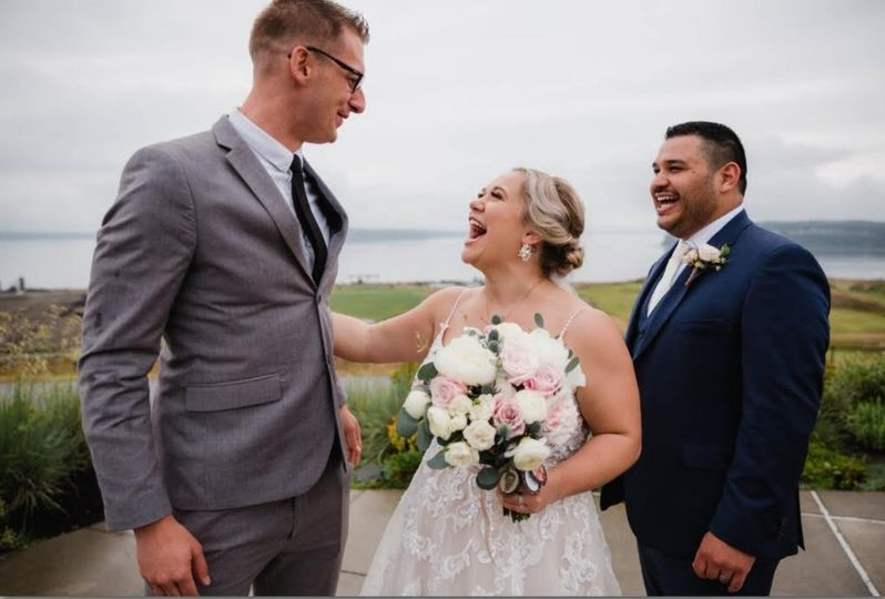 Couple laughing with officiant