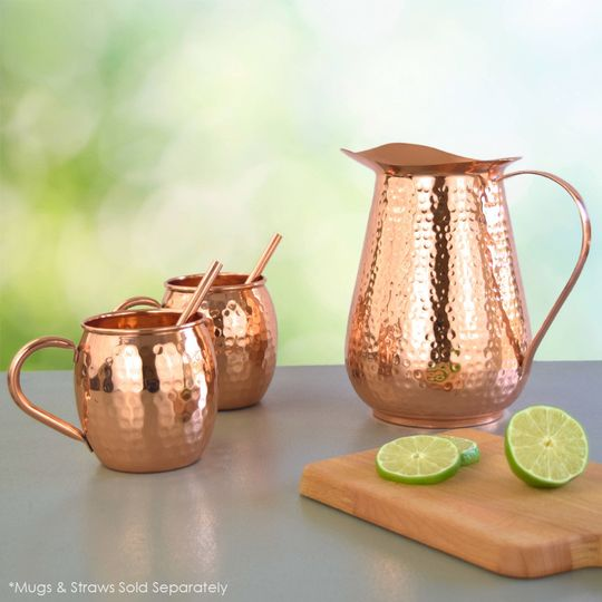 copper pitcher with mugs and straws