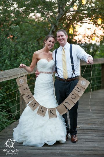 Bride and groom holding the sign