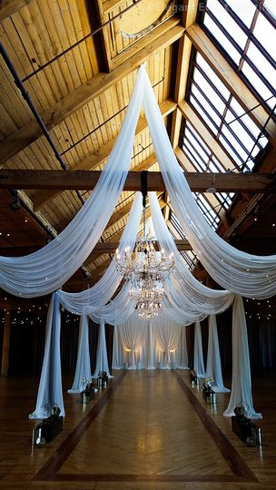 Elegant Event Lighting Ceiling Draping and Crystal Chandeliers with a White Fabric Backdrop done at...
