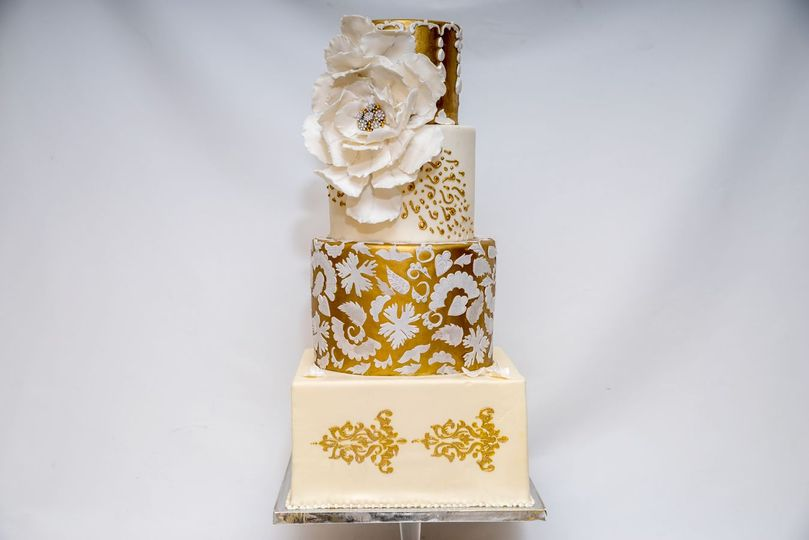 Four tier white and gold cake