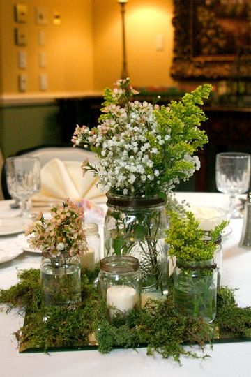 Wedding centerpiece. Mason jars with wildflowers, candles, and moss