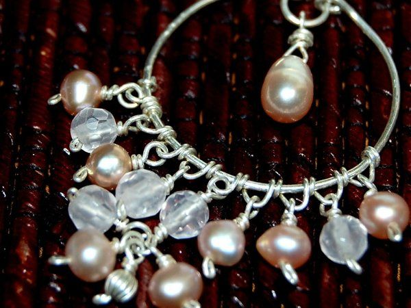 Intricate wirewrapping forms the setting of these chandelier earrings. Soft pink pearls and rose...
