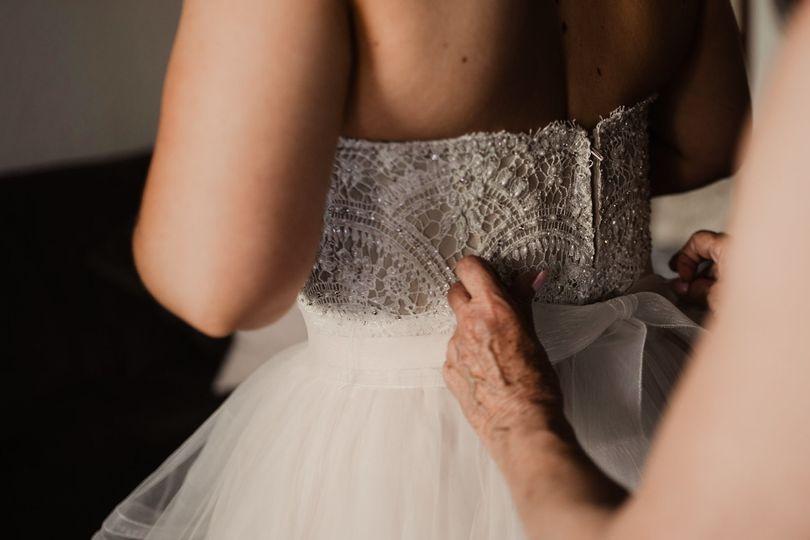 bride putting on wedding dress 51 1064385 1558727570