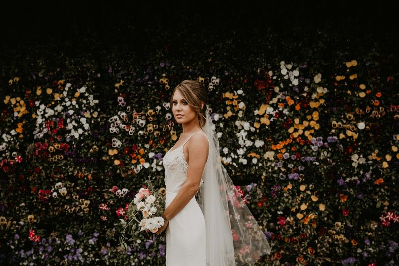 Beautiful bride by the flower wall
