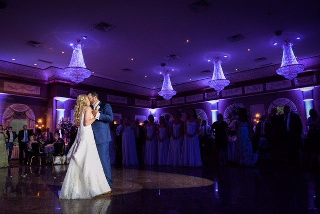 Couple dancing in purple lit ballroom