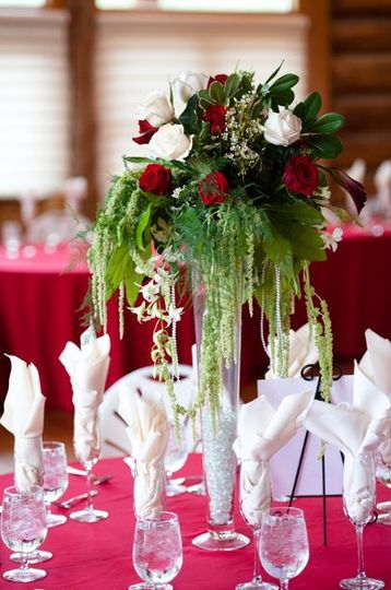 Tall wedding centerpiece with red and white roses, green hanging amaranthus, orchids.