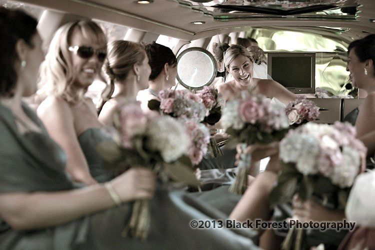 Bride and her bridesmaids during the limo ride to the church. Candid photography