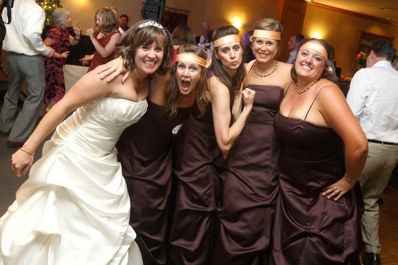 Fun photo of the bride and her bridesmaids on the dancefloor at the reception