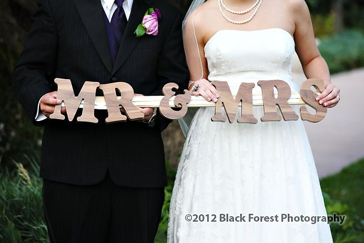 bride and groom holding a handmade sign for the new Mr. and Mrs.