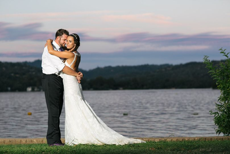 Newlyweds hugging by the lake