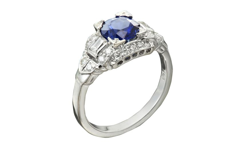 A classic engagement ring with a round sapphire center stone. Around the sapphire there are both...