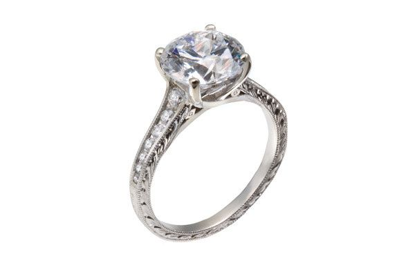 A lady's vintage and diamond engagement ring with a round diamond center stone, round diamond...