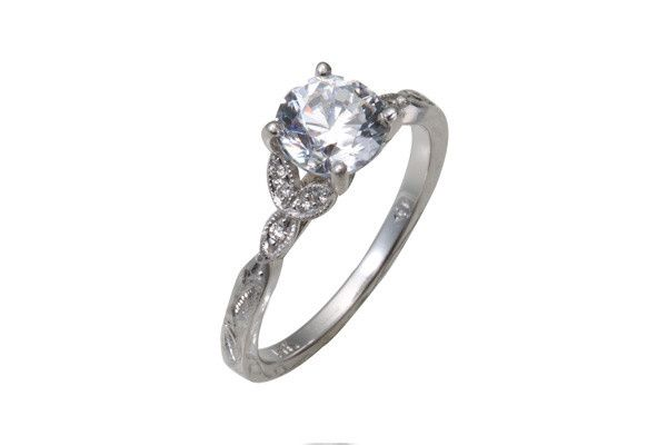 Vintage style engagement ring with bead set leaf elements and hand engraving.