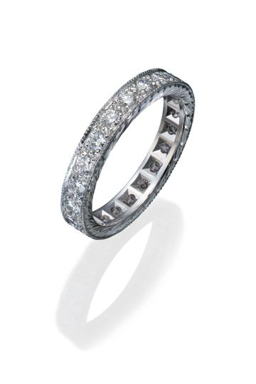 A platinum and diamond eternity band with hand engraving and milgrained edges.