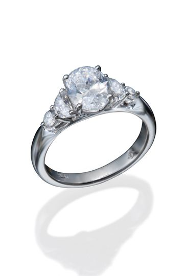 A classic diamond engagement ring with an oval diamond center, half moon, and round diamond accents...
