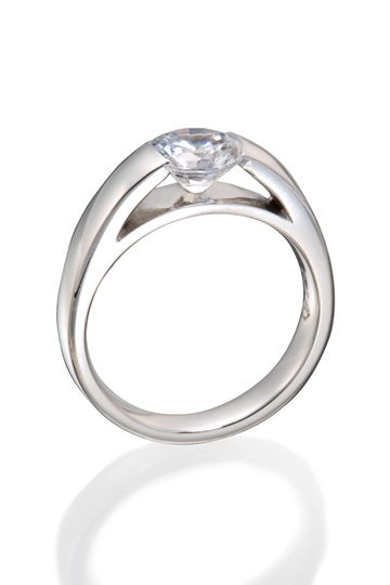 "A highly modernized diamond engagement ring with a round diamond in a ""tension setting""."