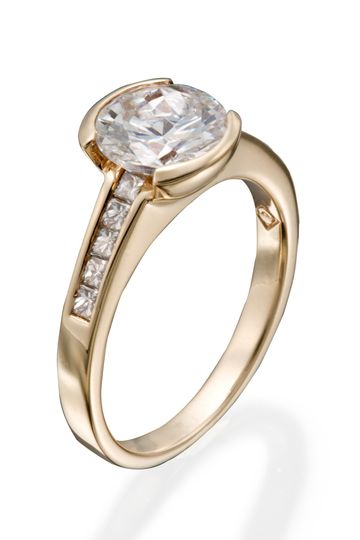 A modern engagement ring with a round diamond center stone and princess cut diamond accents.