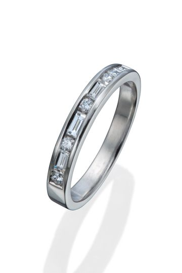 A lady's modern diamond wedding band with both round and straight baguette diamond accents.