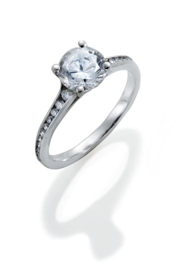 A classic diamond engagement ring with channel set round diamond accents of graduated sizes.