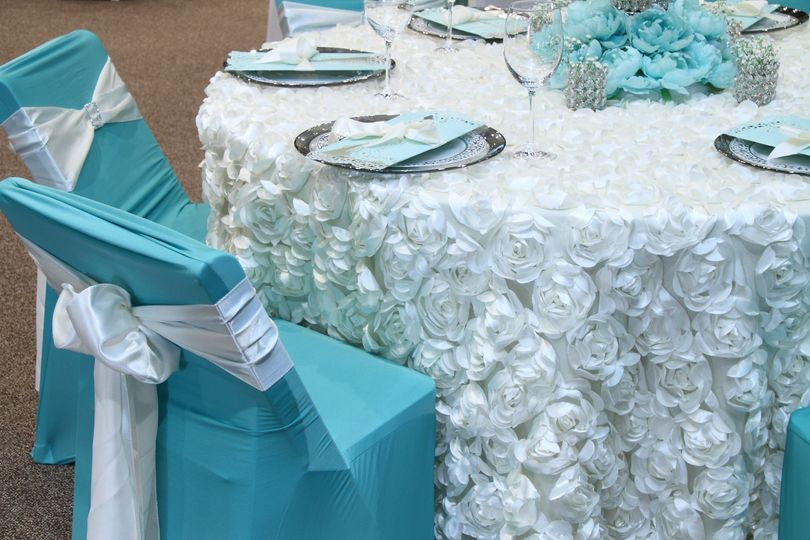 Blue chair covers and white chair bows