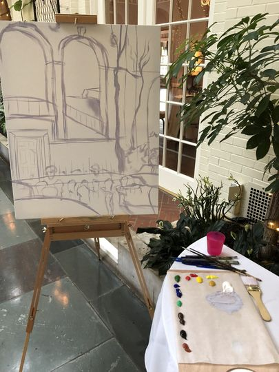 The artist starts by sketching the scene with a thin coat of paint before guests arrive.