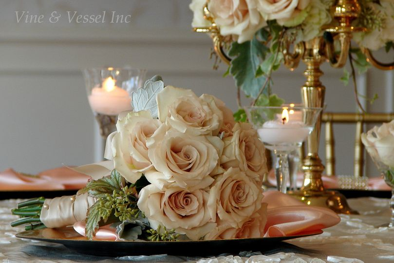 Golden elegance with creamy roses and petite candelabra on a shimmering golden cloth.