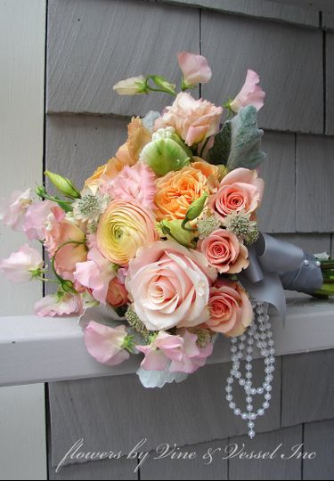 Peachy spring bouquet with pearls and silver gray satin wrap.