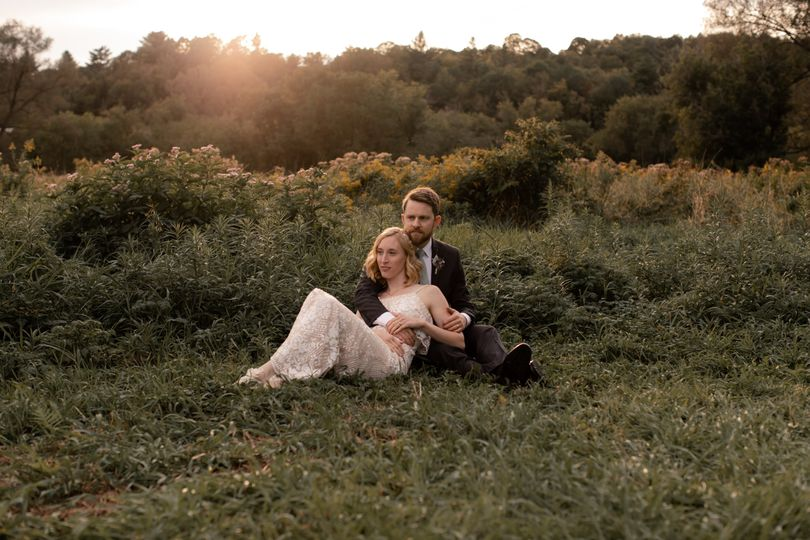 Newlyweds lying on the grass | @cemorelisphotography