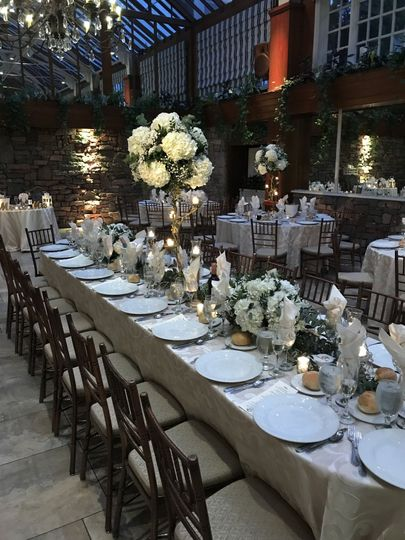Beautiful tables cape of eucalyptus garland, flowers and candelabras in the Winter Garden Room