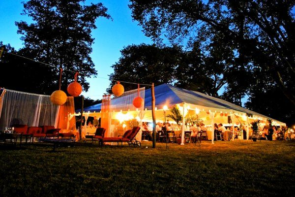 A relaxing lounge is situation next to the main tent for a wedding reception at a private residence...