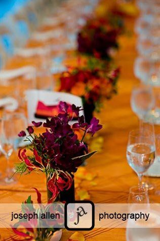 Vibrant floral centerpieces with bumper car illustration table number for wedding reception at...