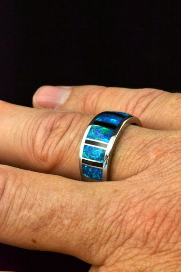 Man's wedding band in sterling silver inlaid with black onyx and lab created opal.  This band is...