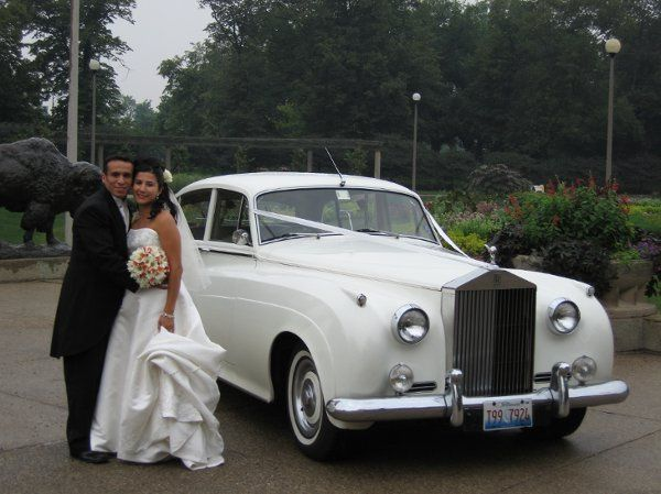 "Another happy couple posing by our 1962 ""Silver Cloud"" Rolls Royce Limousine."
