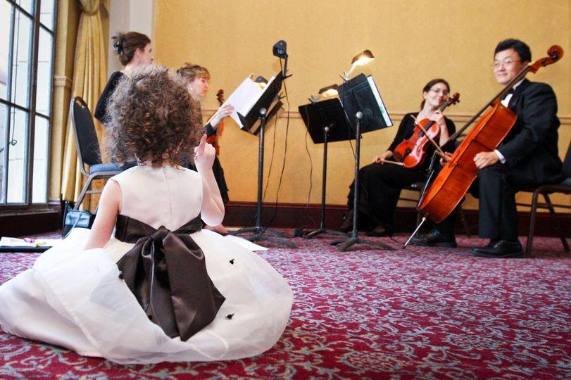 Flower girl watching the string quartet
