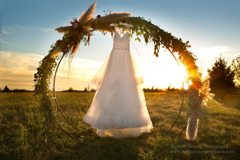 Wedding dress hanging on arch | Memory Keeper Photography