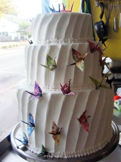 Three tiered cake with buttercream frosting and paper cranes.