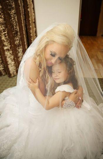 Bride hugging the flower girl
