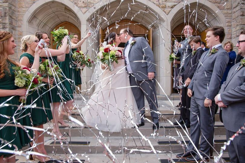 Excitement outside of a church with kissing couple.  Portrait Taken by Lovely Day Photo