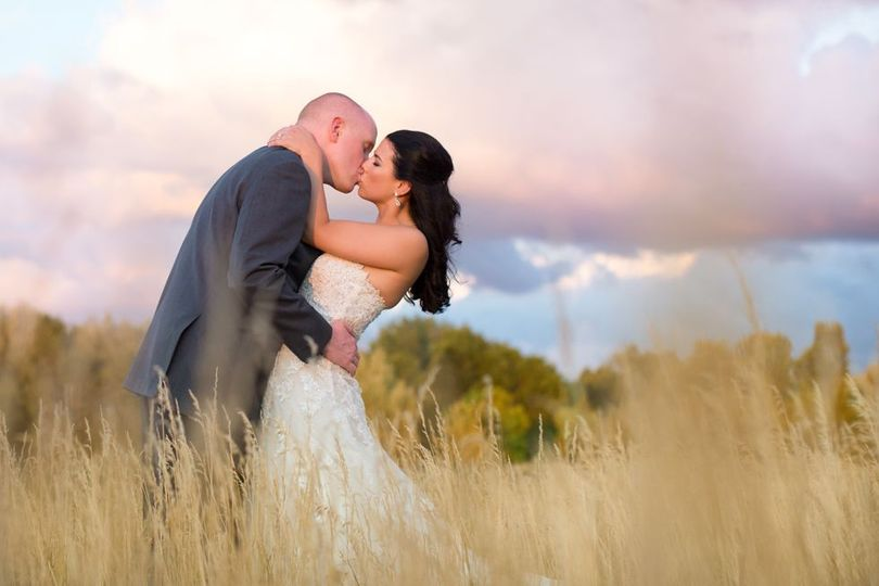 Couple kissing in a field with tall grasses, portrait taken by Lovely Day photo