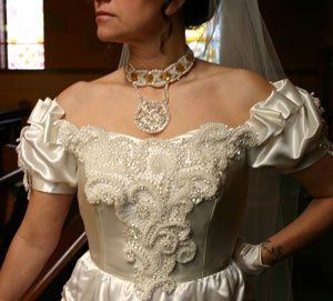 This gorgeous Victorian-style ivory satin gown has elaborate bead work covering the center front of...