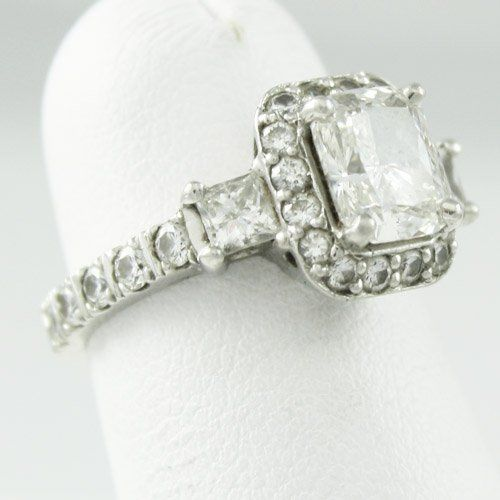 Platinum Band with 1.5ct cushion cut center diamond rimmed with small diamonds with a princess cut...