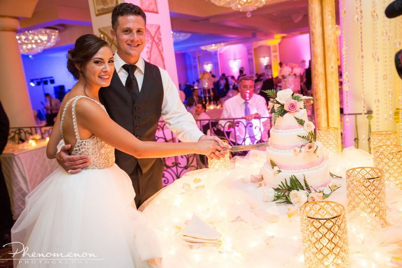 Blue, pink and burnt orange uplighting in the Grand Bellamore Ballroom with upgraded cake table...