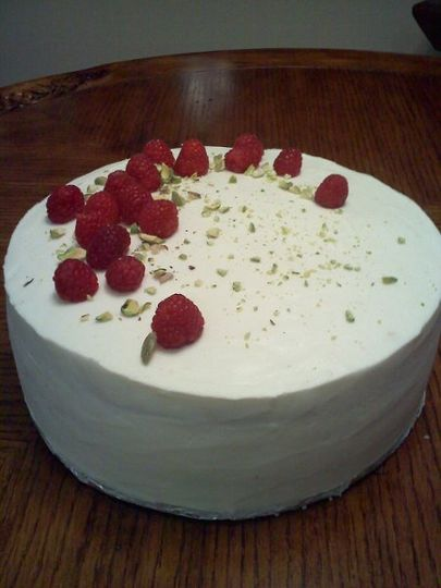 Rose water flavor cake with raspberries and pistachio nuts and butter cream frosting