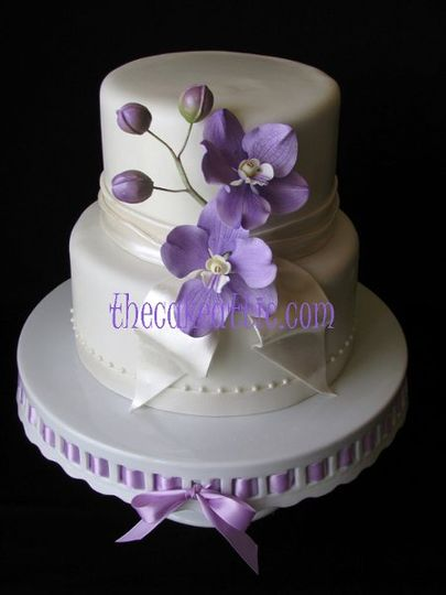 Fondant two tier cake with sugar sash, ribbon and pearls. Lilac Vanda orchids are also hand-molded...
