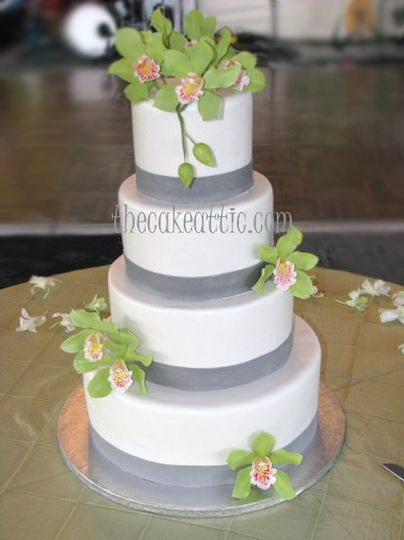 Four tier fondant cake with silver sugar ribbons and green orchids.