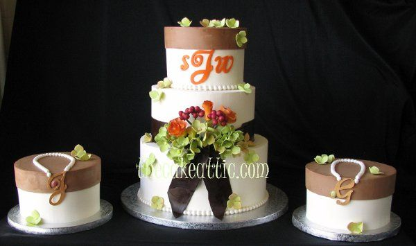 Buttercream cake with fondant sash and sugar flowers. Sides cake have sugar necklaces with the...