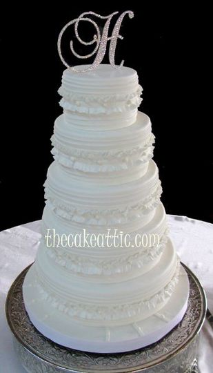 Ruffled and pleated cake with small buttons. Covered in fondant with sugar paste decorations.