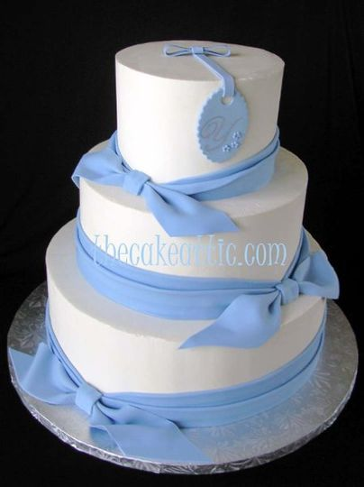 Buttercream cake decorated with sugar sash and ties. Topped off with a monogrammed sugar tag.