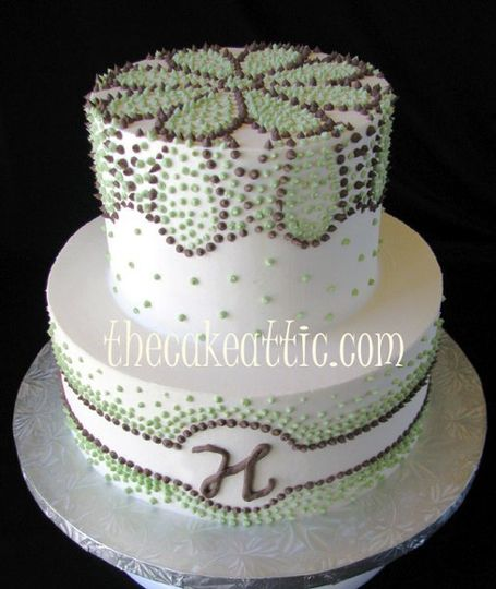 Buttercream cake with a piped buttercream design in chocolate brown and green.